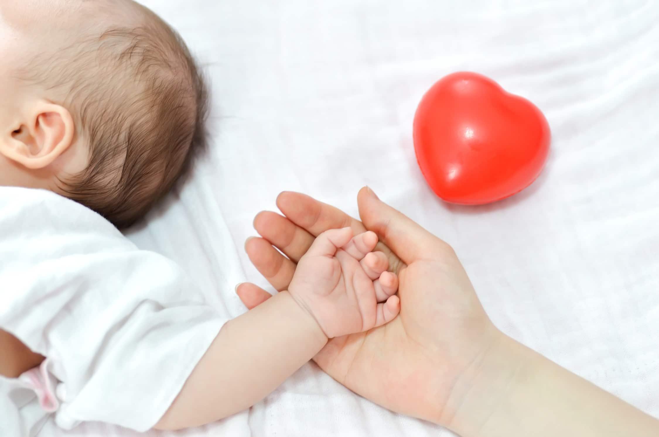 אמא ותינוק לצד בלונים ליולדת מבית מסיבלנד